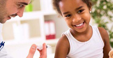 Um homem dando vacina no braço de uma criança